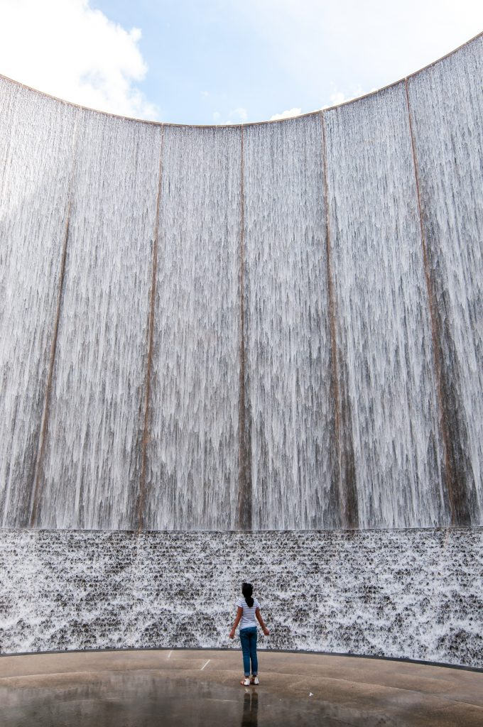 woman standing in front of the houston waterwall, one of the most famous houston waterfalls