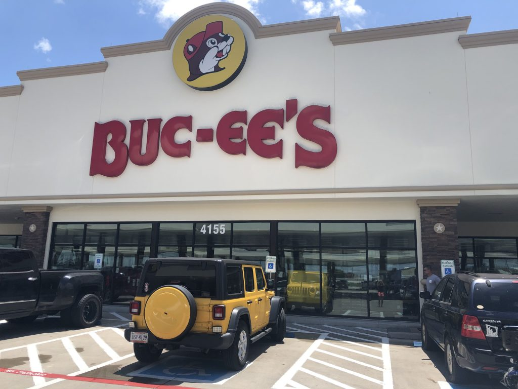 front facade of buc ee's travel center with yellow jeep parked in front