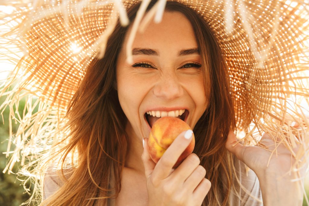 young brunette woman in a straw hat eating a peach