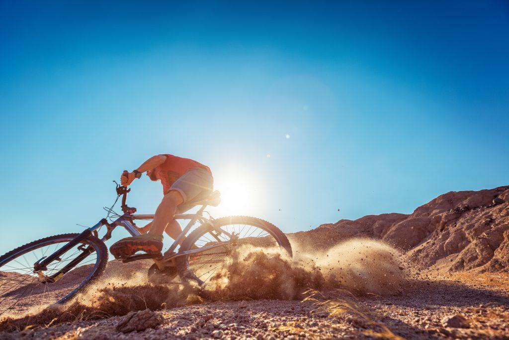 man biking in the desert on a sunny day