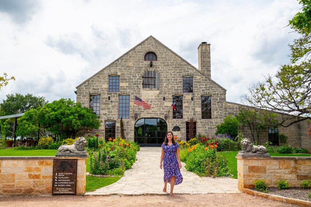 kate storm standing in front of the becker vineyards tasting room, one of the best wineries in fredericksburg texas