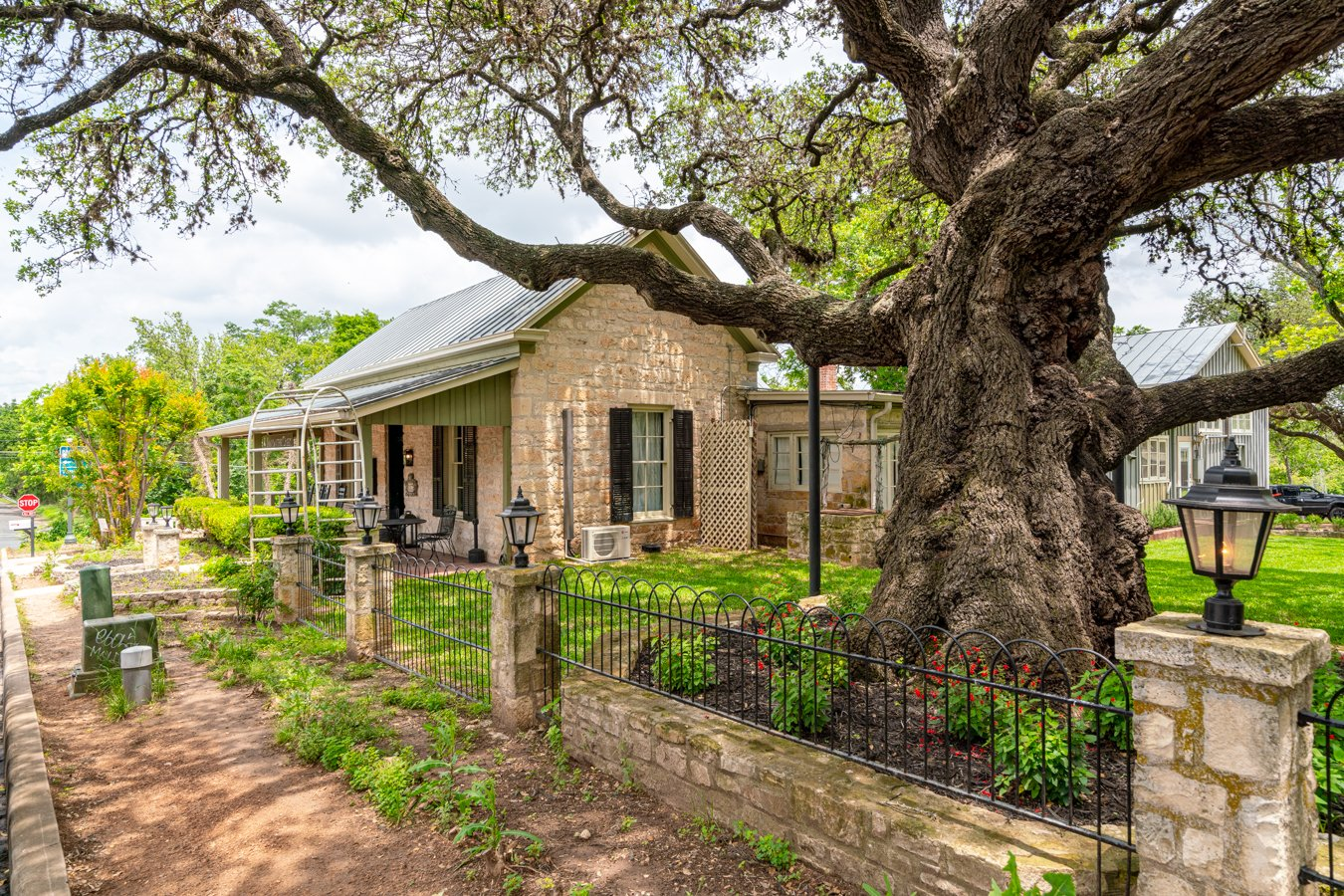 small limestone building under a large live oak in fredericksburg, one of the best texas hill country towns to visit