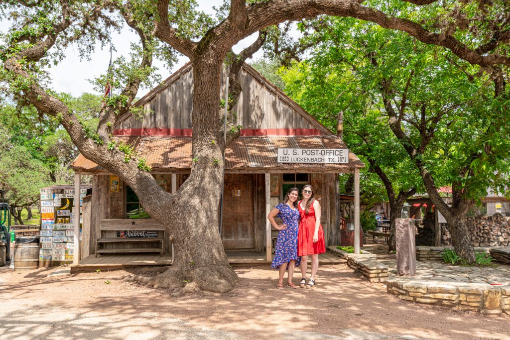 kate storm and allison green in front of luckenbach texas post office, one of the best small towns in hill country texas