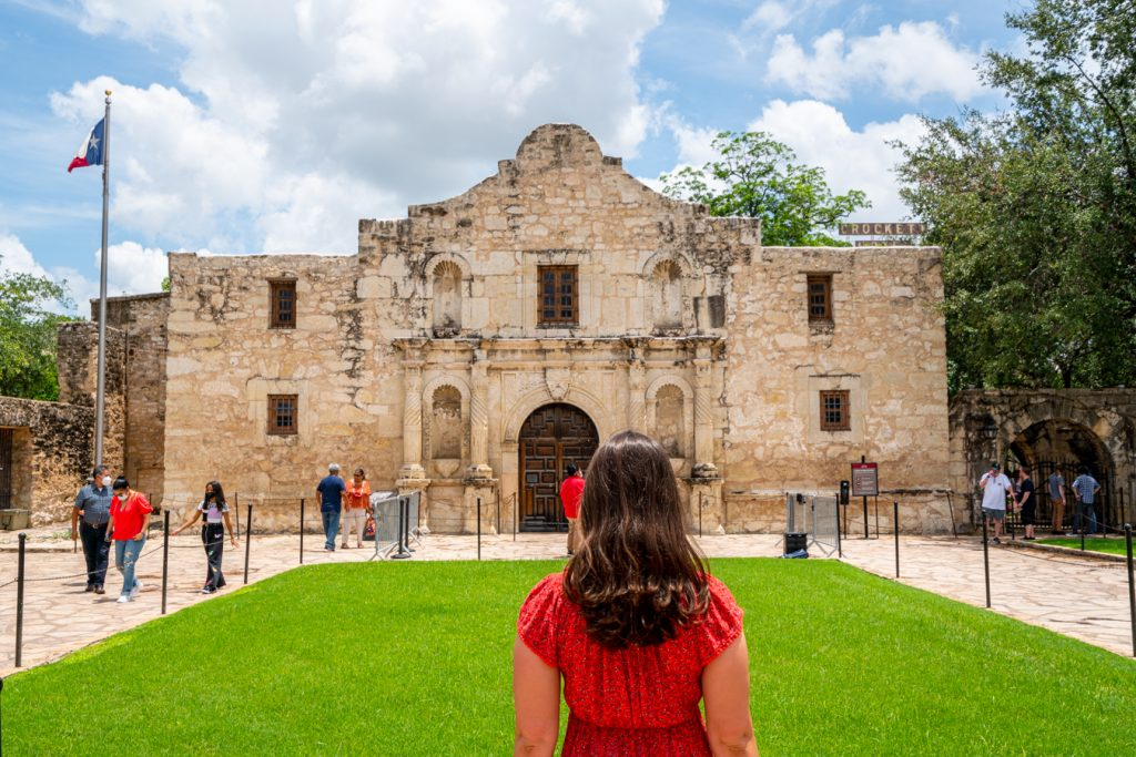 kate storm in a red dress standing facing the alamo when visiting the alamo in san antonio tx