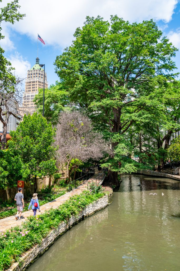 couple walking along the river walk in san antonio, the subject of famous songs about texas