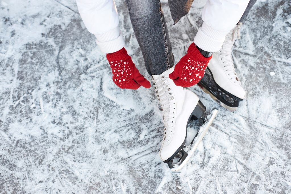 woman wearing red gloves lacing up ice skates. ice skating is one of the best houston christmas events