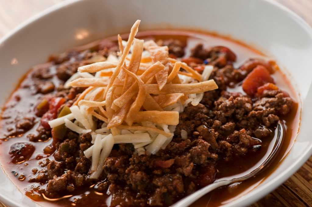 white bowl of texas chili topped with cheese