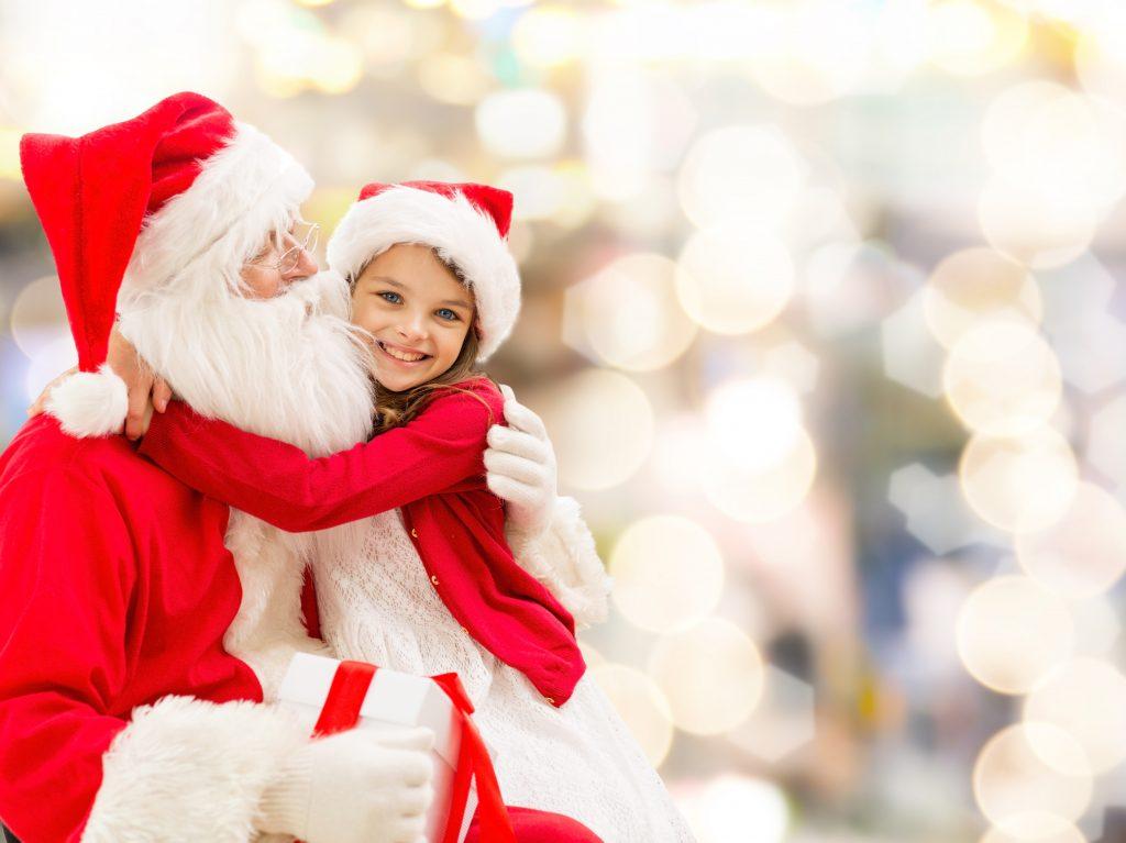 young girl hugging santa claus