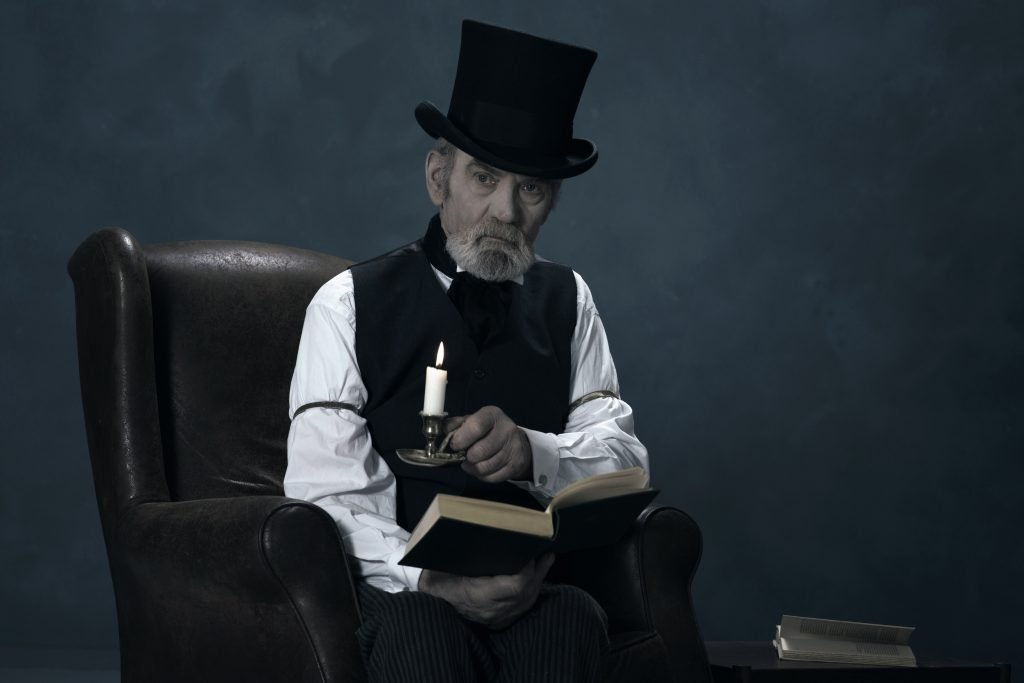 photo of ebenezer scrooge character from a christmas carol sitting in a chair
