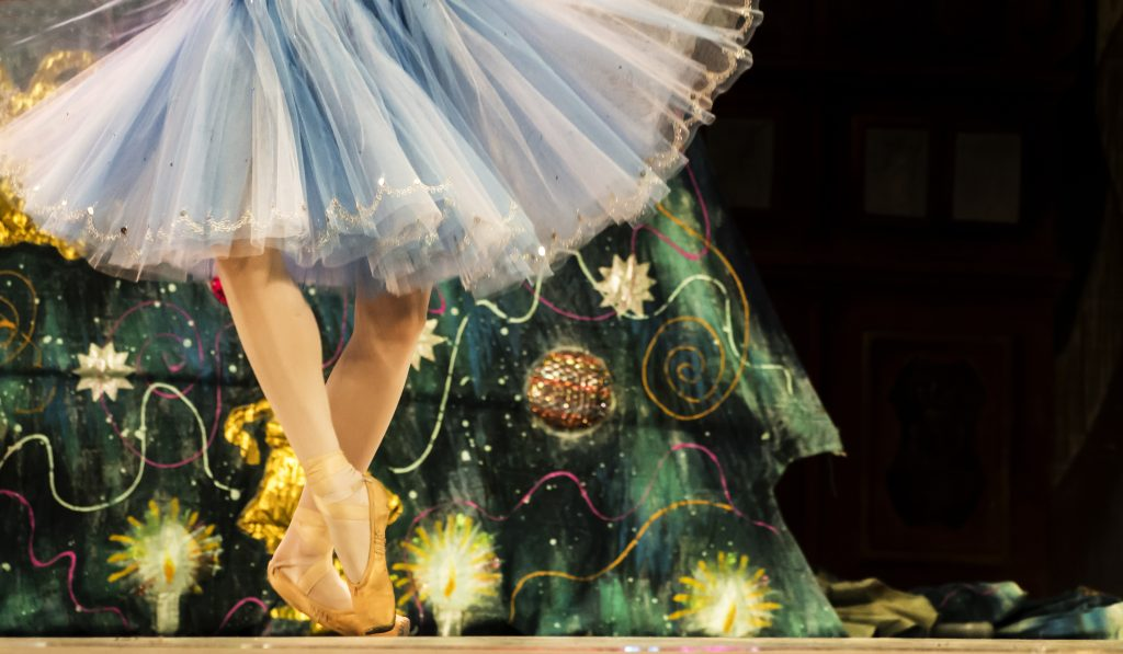 feet of a ballerina in a blue dress in front of a christmas tree. going to see the nutcracker is one of the best christmas events in houston december