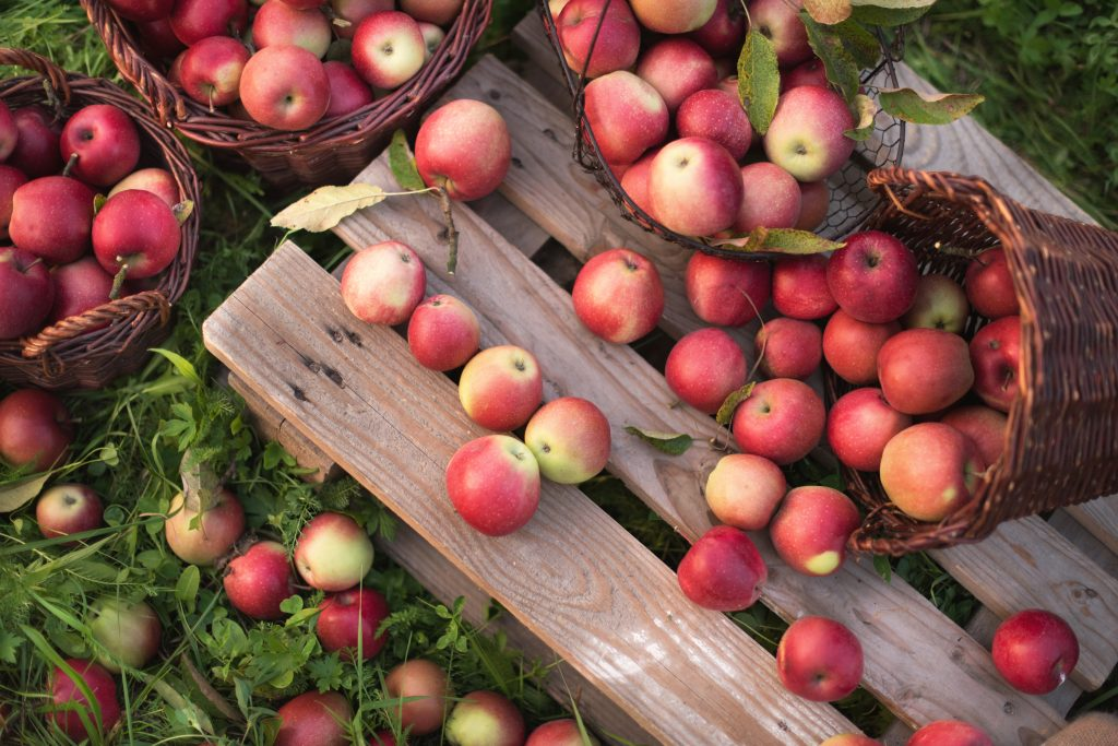 red apples spilling out onto a wooden table