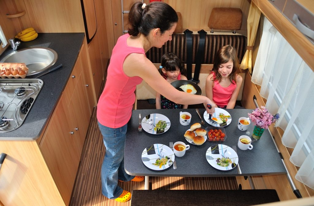 woman in a pink tank top serving dinner to 2 children when rv camping big bend national park