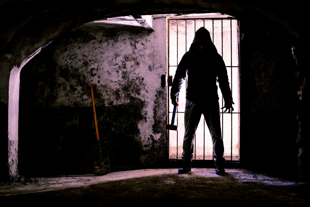 scary dark man holding a weapon in a dungeon, forth worth haunted houses