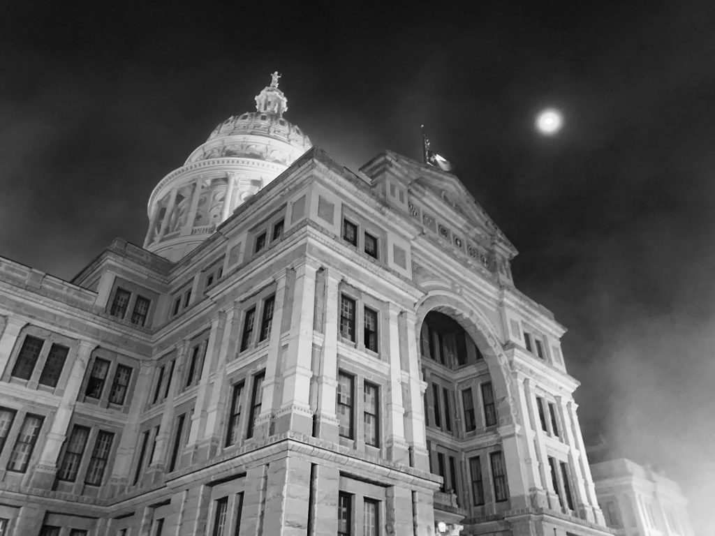 black and white photo looking up at the texas capitol building in austin tx at night