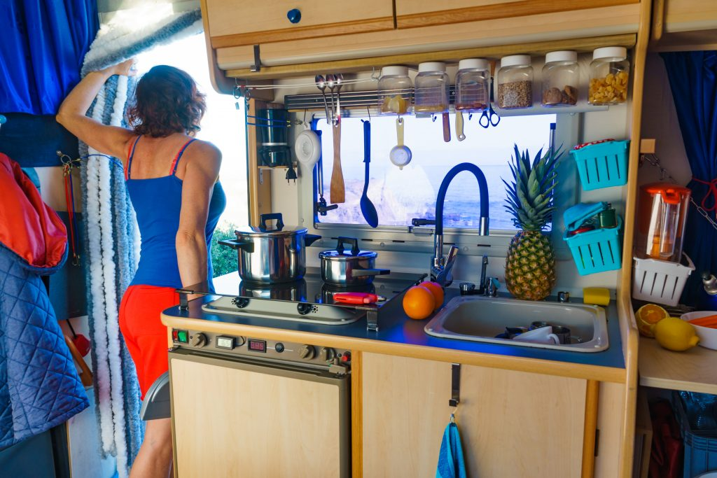 woman standing in the doorway of an rv with the rv kitchen visible next to her