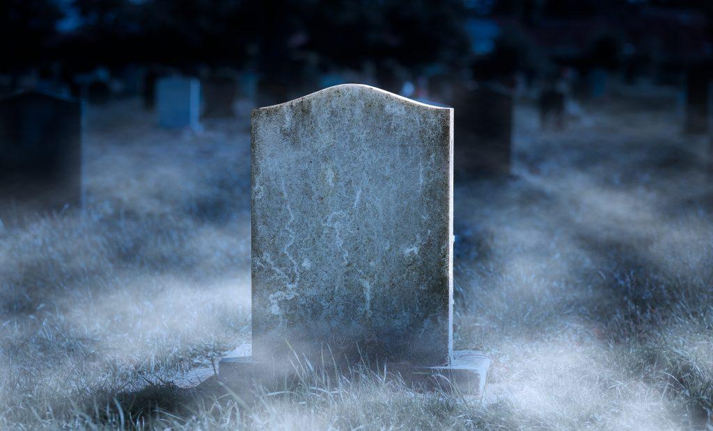 creepy gravestone in a cemetery at night
