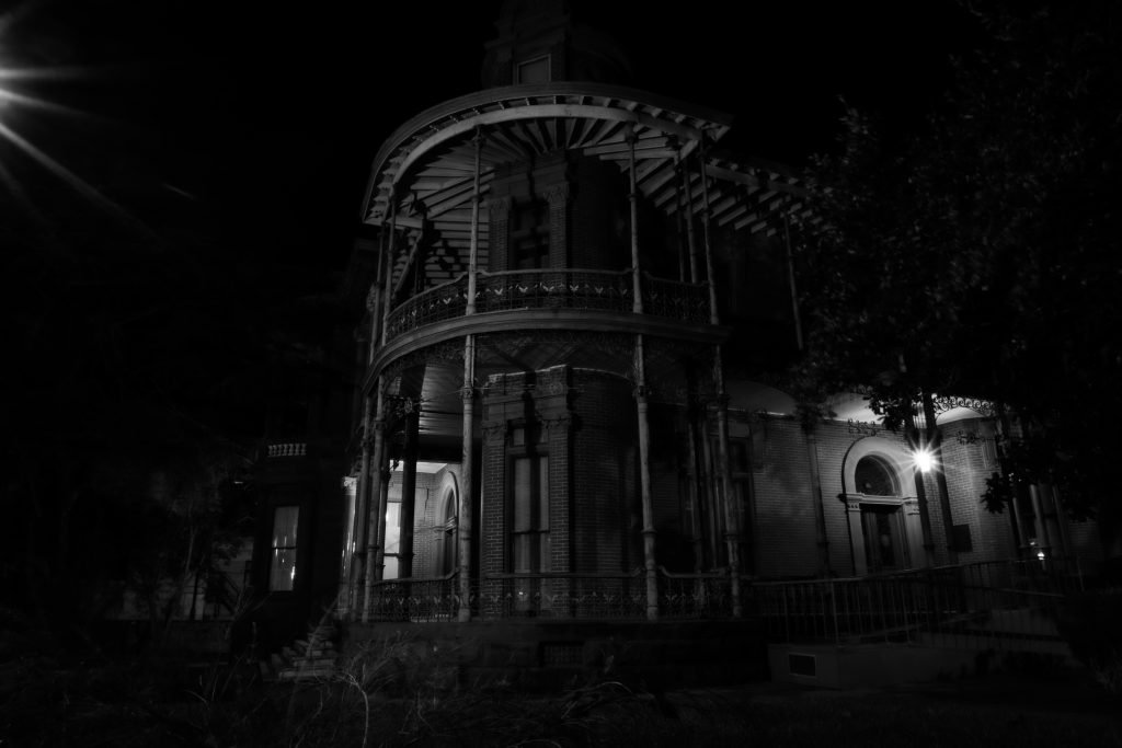 very dark photo of a spooky victorian mansion in austin at night