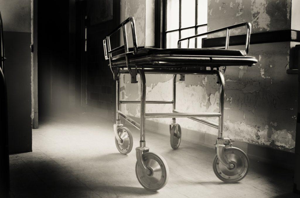 old fashioned gurney in a haunted asylum