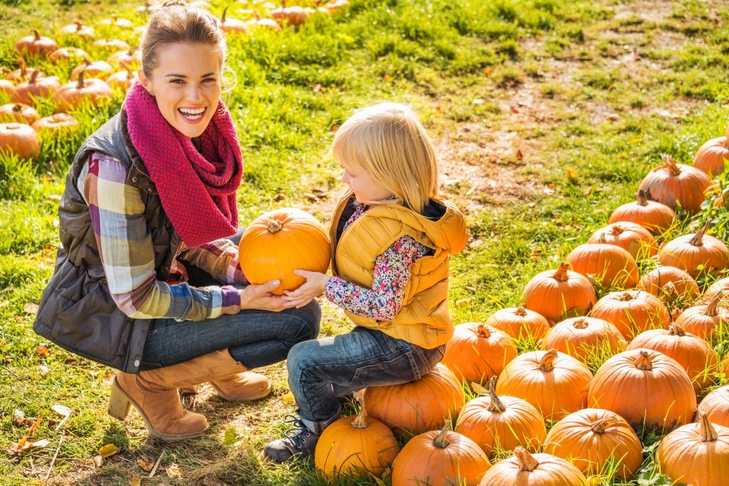 young woman posing with her small daughter in a pumpkin patch dallas