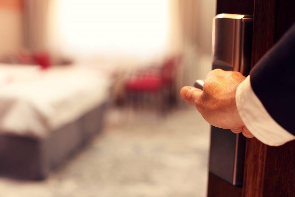 man's hand opening a hotel room door