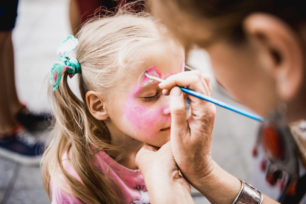 young girl getting her face painted at fall festival austin