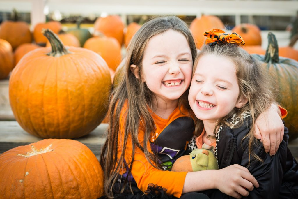 two young girls hugging each other in a pumpkin patch