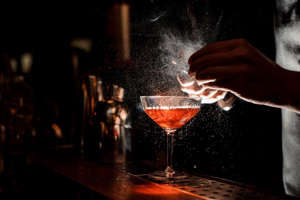 bright red cocktail being made in a dark bar