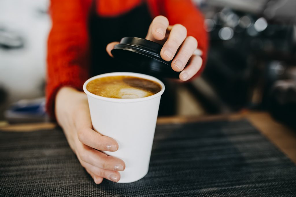 barista handing a coffee in a white paper cup to a customer