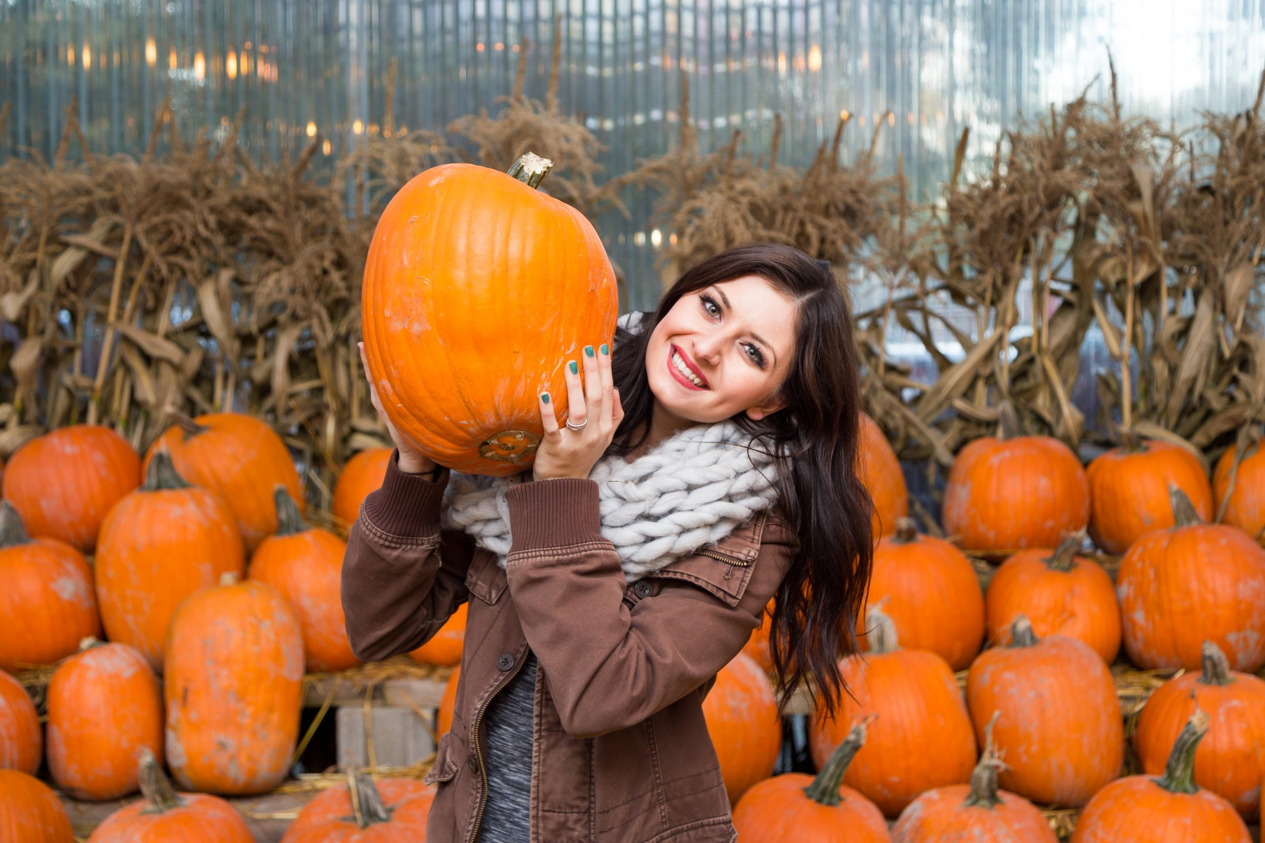 young woman with brown hair holding up a pumpkin at one of the best pumpkin patches in houston texas