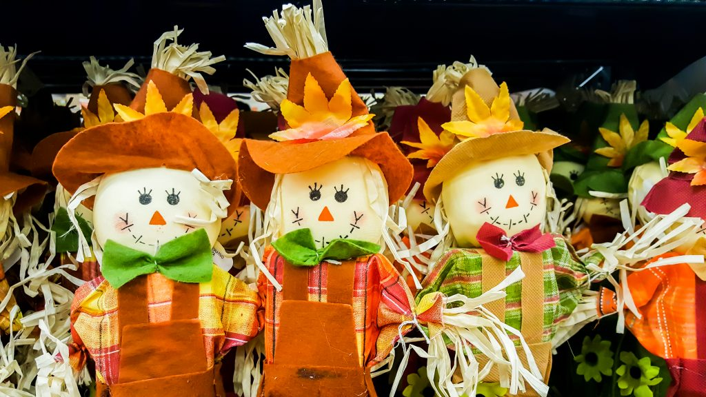 group of four cute scarecrows dressed in orange