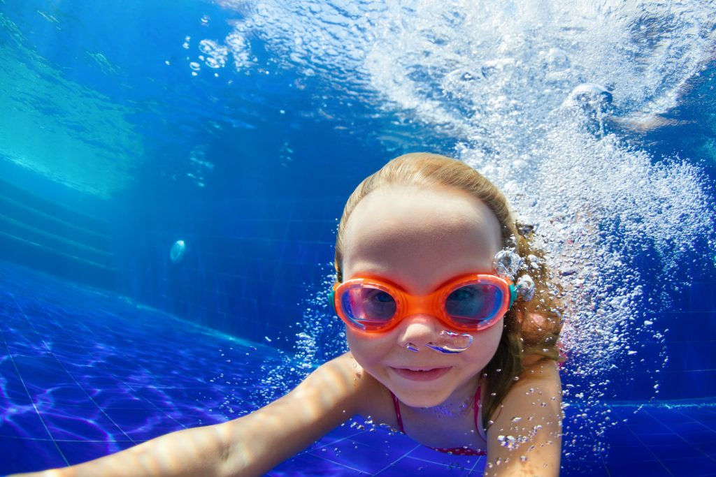 underwater photo of a young girl swimming in a pool with orange goggles on