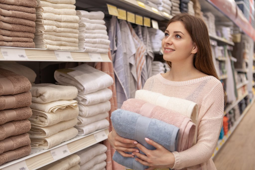 young woman shopping for towels in a home goods store