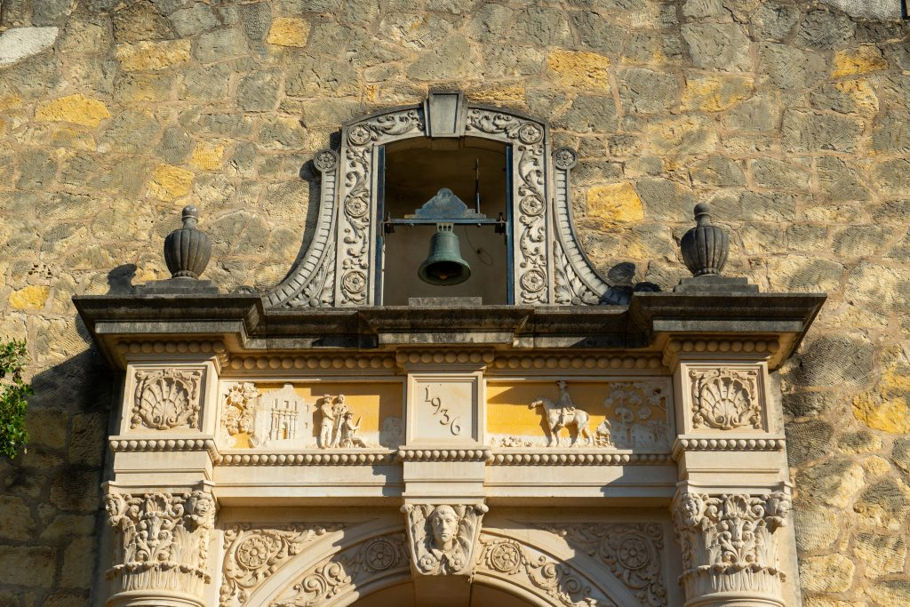 bell hanging over the ornate door of the gift shop, visit the alamo san antonio texas