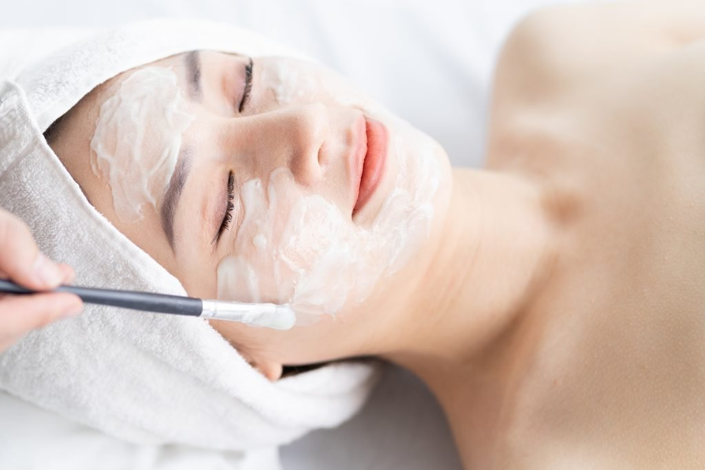 young woman with her hair wrapped in a white towel receiving a facial treatment