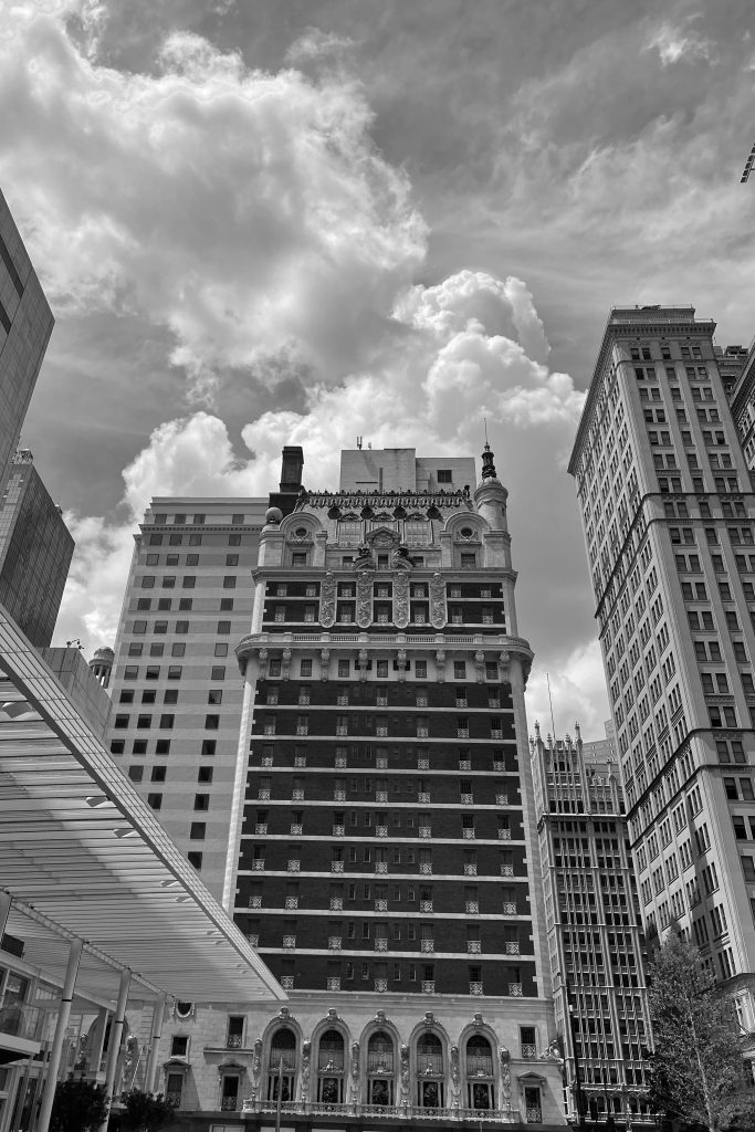 front facade of adolphus haunted hotel in dallas texas in black and white
