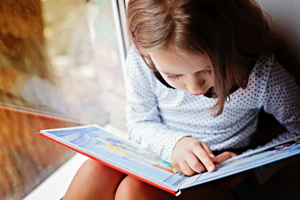 little girl with brown hair reading a picture book