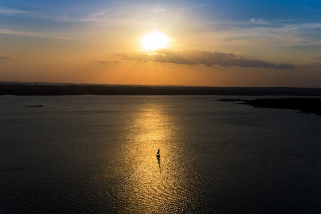 view of a sailboat on lake travis at sunset, one of the best austin evening activities