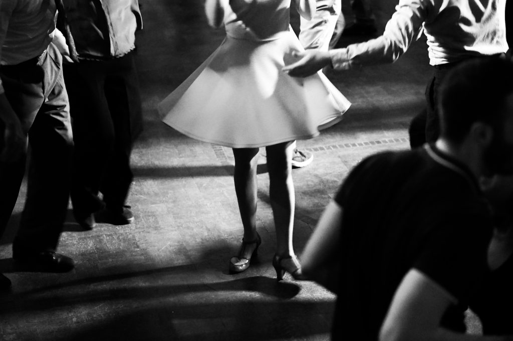black and white photo of people dancing in a dance hall