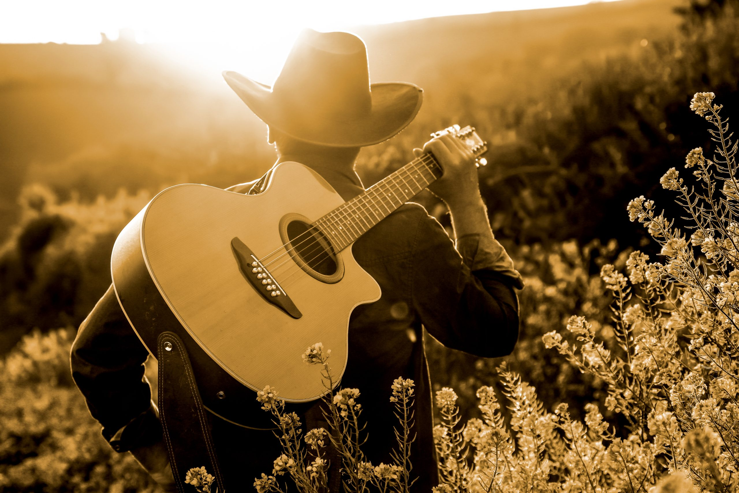 man in a cowboy hat carrying a guitar at sunset, representative of famous songs about texas
