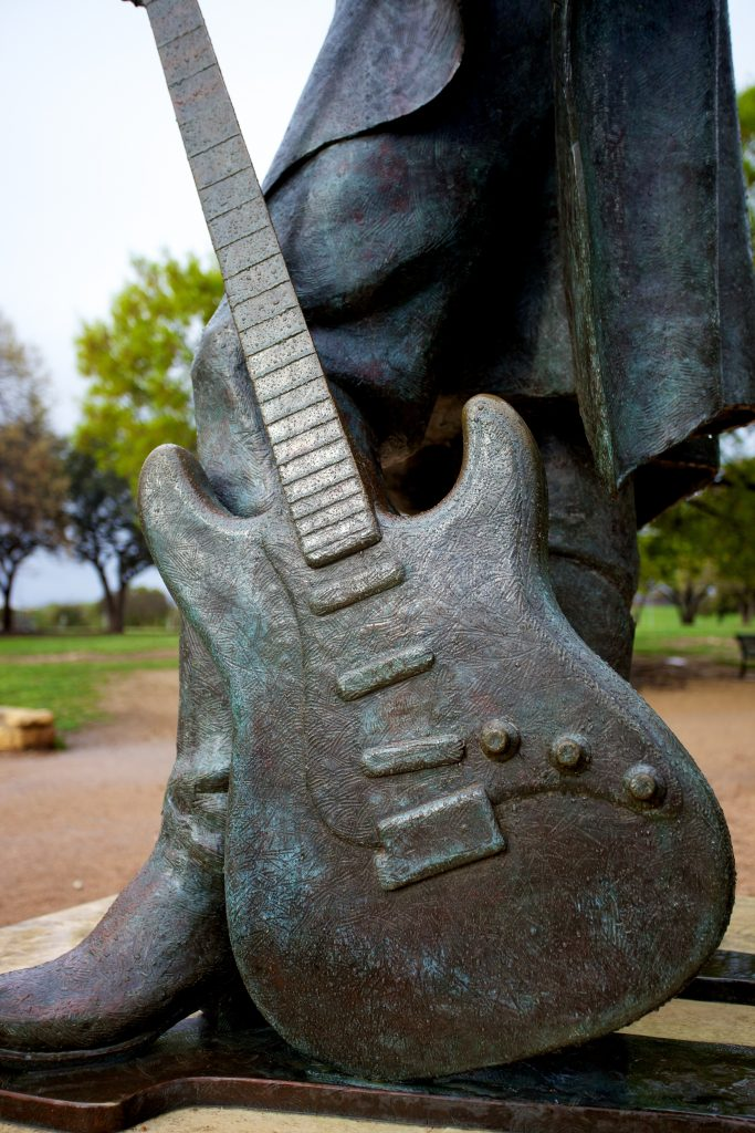 statue of guitar of stevie ray vaughan in austin texas, who sang celebrated songs about texas